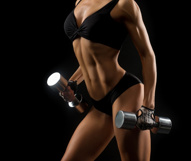 Женщина фитнеса с совершенным телом держа гантели
