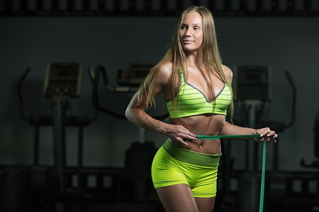 Fitness woman with roulette measures the circumference of the abdomen