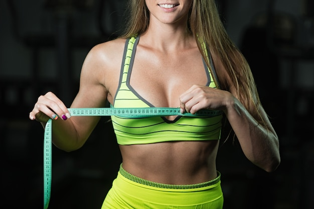 Fitness woman with roulette measures the circumference of the thorax close up