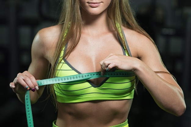 Fitness woman with roulette measures the circumference of the thorax