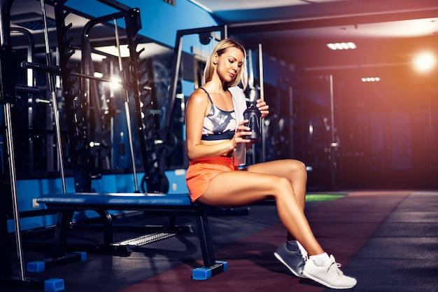 Fitness woman with shaker posing in the gym