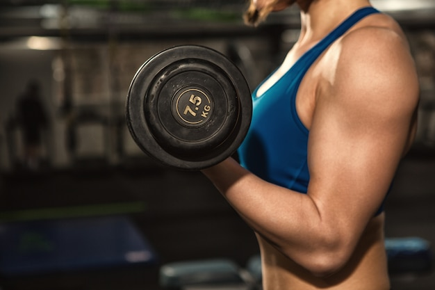 上腕二頭筋のカールを行うスポーツウエアで強い引き締まったボディを持つフィットネス女性