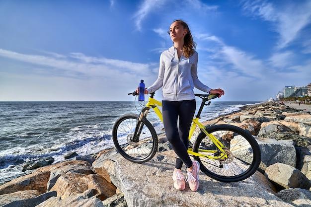 Фитнес женщина с желтым велосипедом