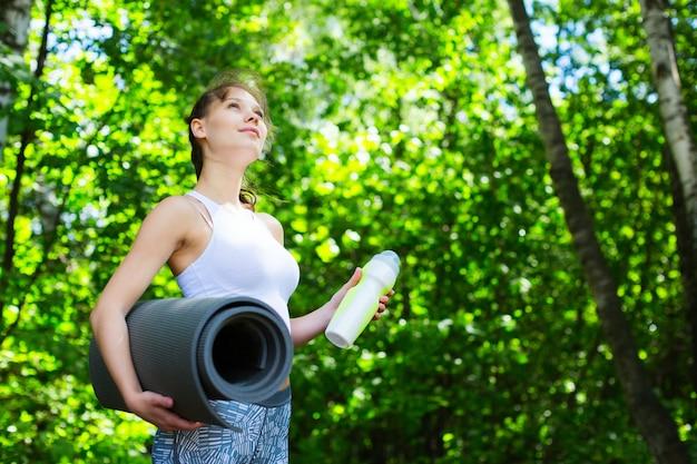 Женщина фитнеса с циновкой йоги outdoors.