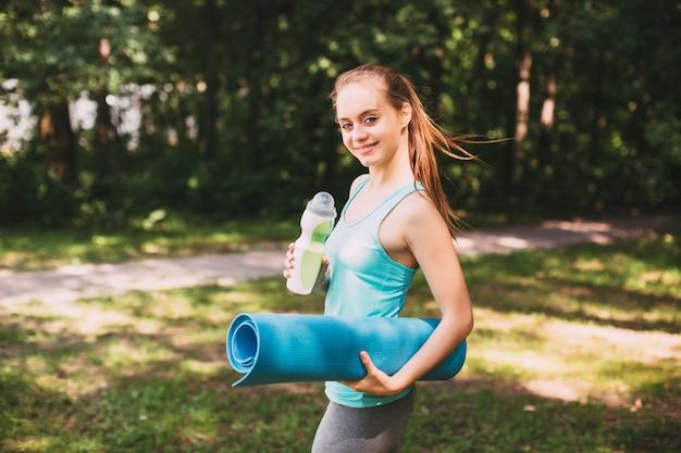 Женщина фитнеса с циновкой йоги на открытом воздухе
