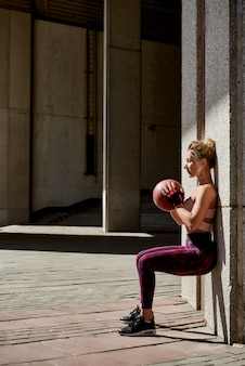 Fitness woman working out at outdoors gym using medicine ball.