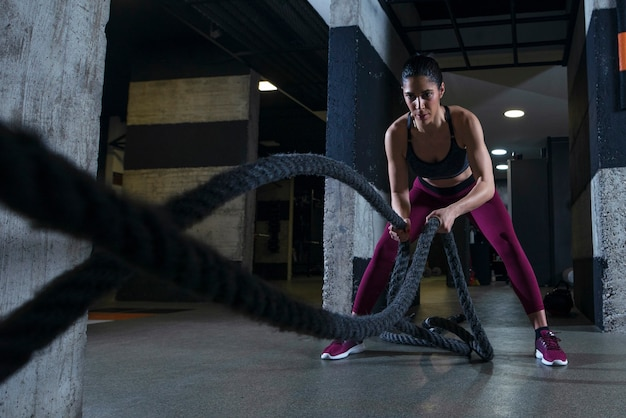 Fitness woman working out with battle ropes in the gym