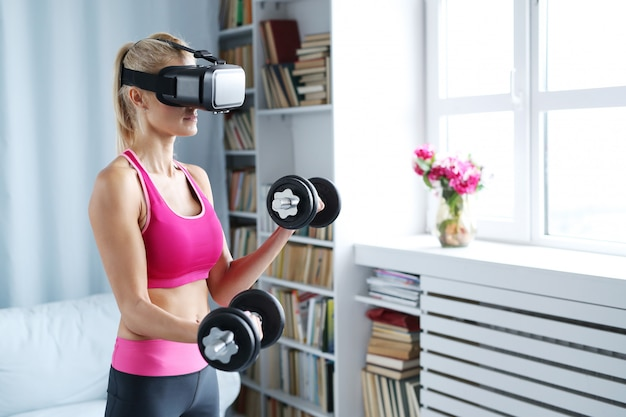 Fitness woman workout with dumbbells and vr headset