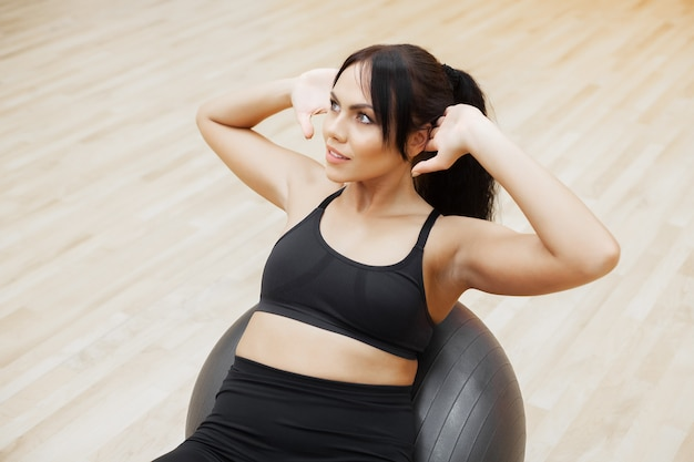 Fitness woman, young attractive woman doing exercises using ball