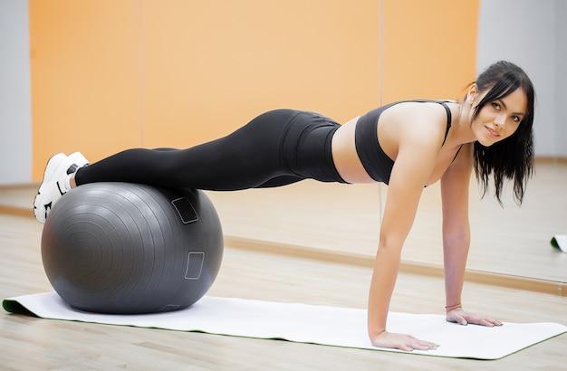 フィットネスの女性。ボールを使用して腕立て伏せをしている若い魅力的な女性。