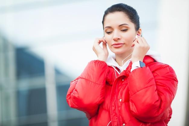 フィットネスの女性。空港近くのイヤホンでスポーツウェアの若い女性。