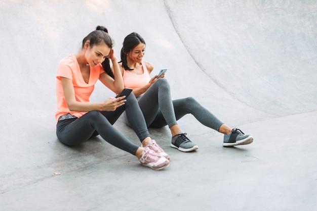 콘크리트 운동장에 앉아있는 동안 미소하고 핸드폰을 함께 들고 운동복 피트니스 여성