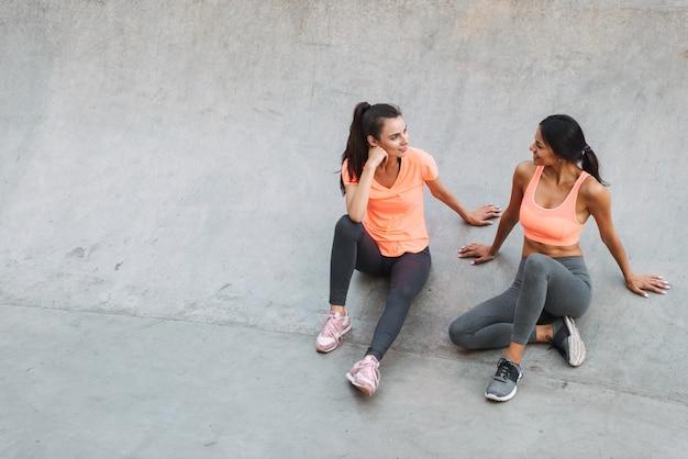 운동복 피트니스 여성 미소하고 콘크리트 운동장에 앉아있는 동안 함께 이야기