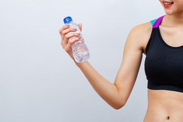 Fitness women lifting up and holding bottle of water