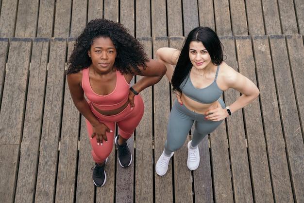 함께 달리는 피트니스 여성. 다른 국적의 운동복을 입고 훈련하는 페미니스트 여성.