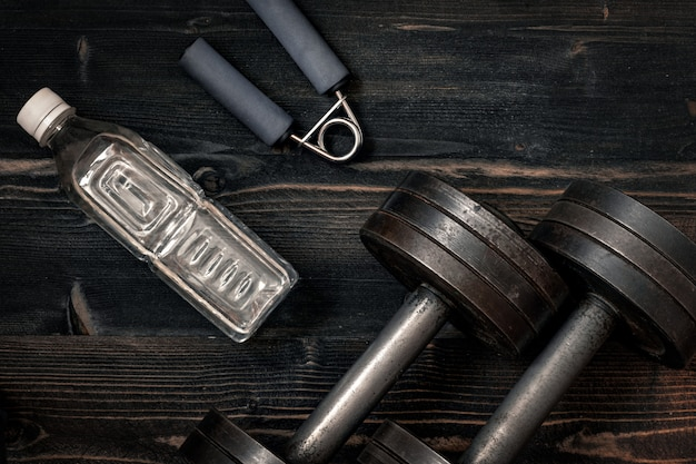 Fitness workout equipment. dumbbell or barbell on a wooden floor surface. flat lay desaturated concept