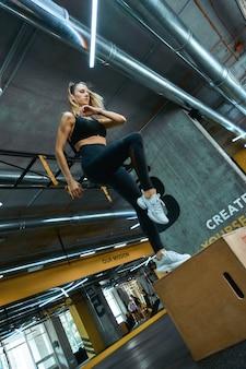 で木製のクロスフィットボックスにジャンプするスポーツウェアのフィットネストレーニングフルレングスの若いアスリート女性