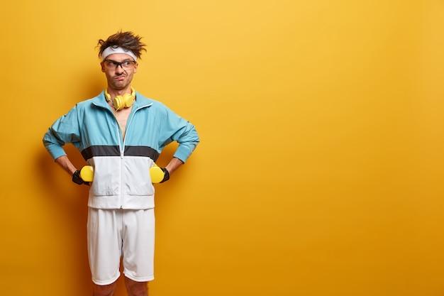 피트니스, 운동, 건강한 라이프 스타일 및 운동 개념. 심각한 결정된 운동가는 허리에 손을 얹고, 아령을 들고, 운동복을 입고 운동을 제어하고, 노란색 벽에 절연