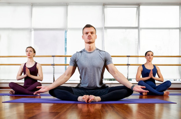 Fitness, yoga and healthy lifestyle concept - group of people doing lotus seal gesture and meditating in seated pose