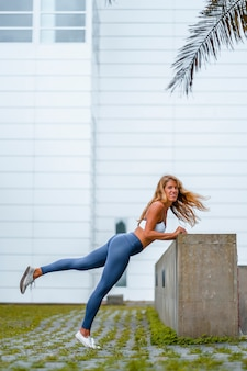 Fitness and yoga session with a young blonde caucasian instructor dressed in a casual outfit with blue maya and a white t-shirt. stretching with a white wall