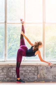 Fitness young businesswoman practicing yoga near the window