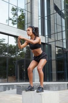 ポニーテールの髪型が屋外で運動し、スクワットをしながらバランスを保つために手を上げる、フィットネスの若いダークスキンモデル。健康的なライフスタイル、開発、スポーツのコンセプト