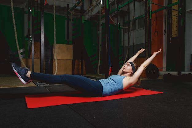 Fitness young girl in the gym doing exercises with abdominals. crossfit