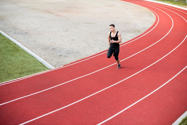 Fitness young male athlete running on race track