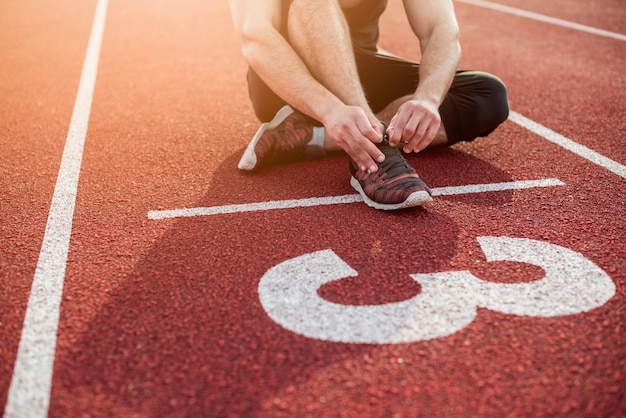 Fitness young man sitting on start line over the red track field Premium Photo