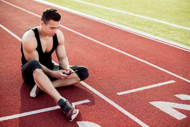 Fitness young man using mobile phone while sitting on race track