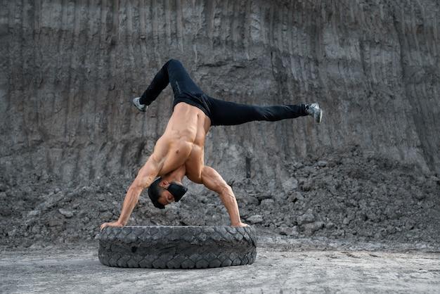 屋外で大きなタイヤで逆立ちをしている裸の胴体を持つフィットネスの若い男。砂の採石場で運動するフェイスマスクの健康でアクティブなスポーツマン。