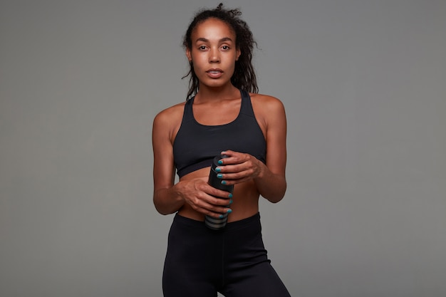 Fitness young pretty dark skinned curly model with ponytail hairstyle being in good physical shape, training in gym every morning before work, isolated