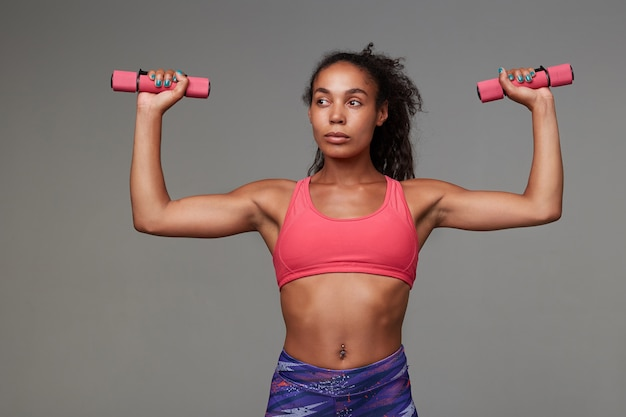 Fitness young slim dark skinned curly brunette female looking aside with folded lips while making exersices with dumbbells, goes in for sport every morning, isolated