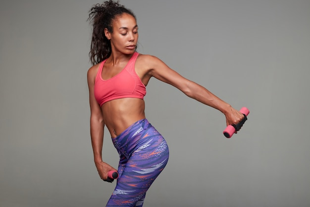 Fitness young slim dark skinned curly woman in pink sporty top and printed leggins doing workout for her hands