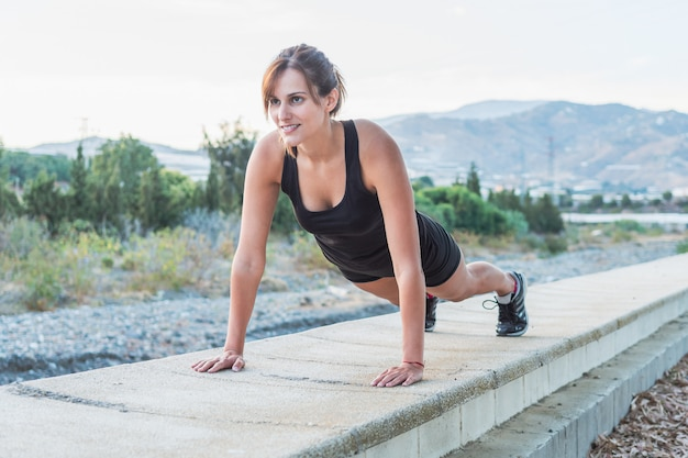 Fitness young woman doing push ups workout in the park