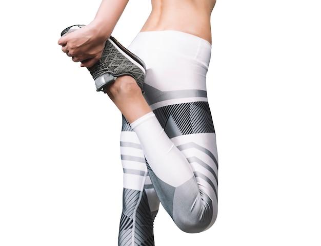 Фитнес молодая женщина делает растяжку, носить белые леггинсы и серые кроссовки.