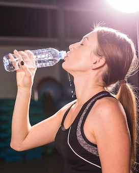 Fitness young woman drinking water from bottle. muscular young female at gym taking a break from workout.