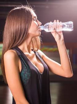 ジムで水を飲むフィットネス若い女性。運動後に休憩を取る筋肉の女性