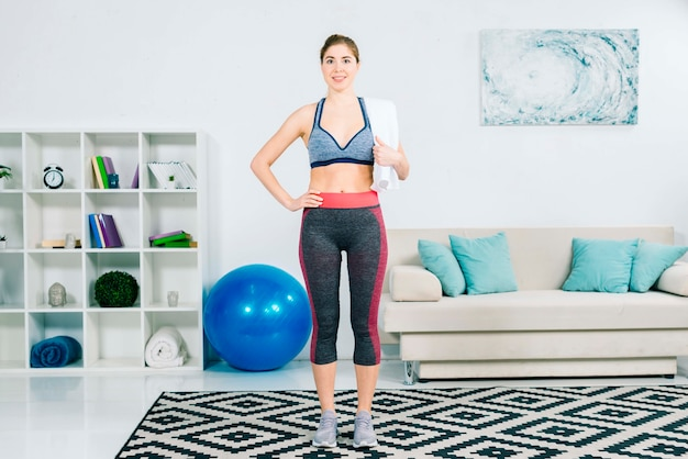 Fitness young woman holding towel over shoulder standing in the living room