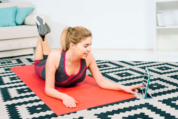 Fitness young woman lying on exercise mat using digital tablet