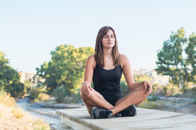 Fitness young woman practices yoga and meditates in the lotus position