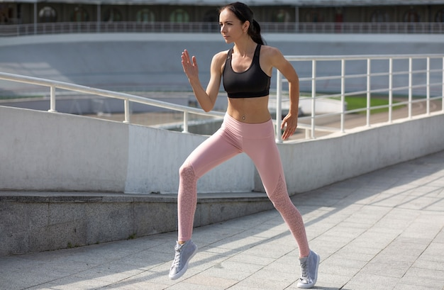 Fitness young woman in a sports clothes is doing fitness exercises at the stadium in the morning. empty space