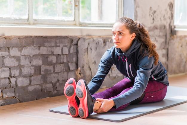 Giovane donna di forma fisica in abiti sportivi che fa esercizio