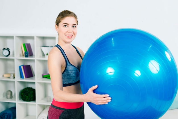 Fitness young woman in sportswear holding large pilates blue ball