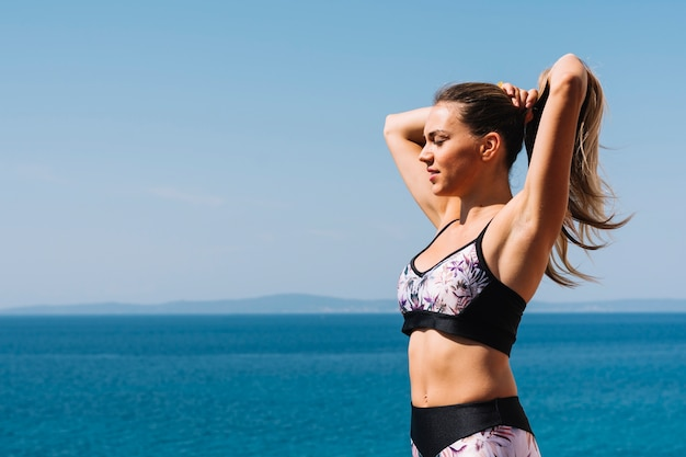 Fitness young woman standing near the blue sea tying her hair