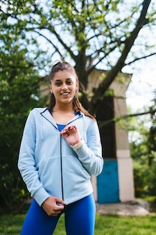Молодая женщина фитнес гуляет в парке и позирует