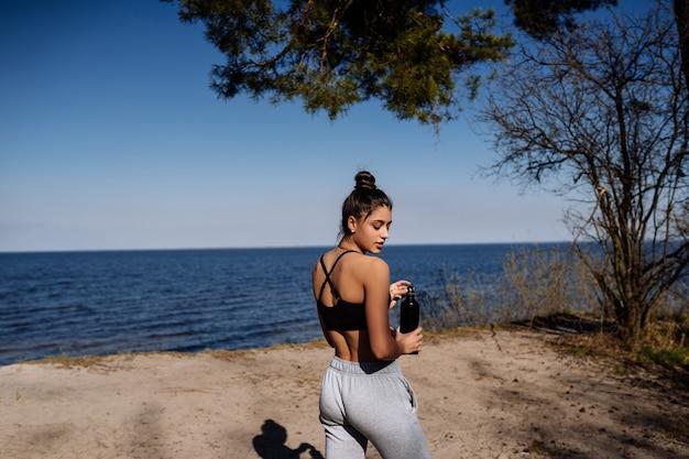 La giovane donna di forma fisica cammina nel parco
