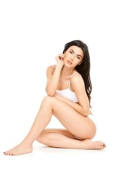 흰색 배경에 앉아 아름다운 몸을 가진 피트 니스 젊은 여자