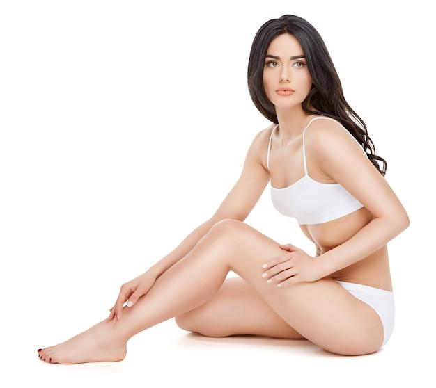Молодая женщина фитнеса с красивым телом сидя