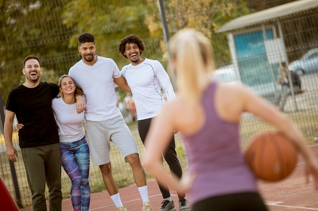 Fitness young woman with basketball ball playing game outdoor with friends